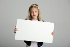 Menina bonito que prende um sinal em branco no cinza imagens de stock royalty free