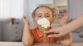 Menina bonito que prova o cone de gelado da mão fêmea, surpresa da infância, petisco vídeos de arquivo