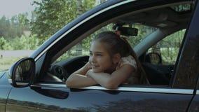 Menina bonito que relaxa e que olha para fora a janela de carro video estoque