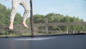 Menina bonito que salta em um trampolim na parte externa do verão