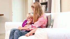 Menina bonito que senta-se com a mãe no sofá vídeos de arquivo