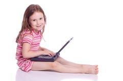 Menina bonito com um portátil Foto de Stock