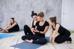 Menina bonito que senta-se e que socializa com o grupo após sua classe da ioga fotografia de stock