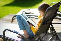 Menina bonito que senta-se em um jardim e que lê um ebook na noite ensolarada do verão fotos de stock