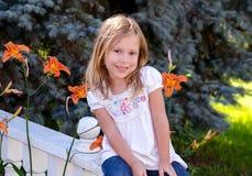 Menina bonito que senta-se em um trilho Fotos de Stock Royalty Free