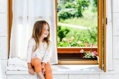 Menina bonito que senta-se em uma janela do banheiro Fotografia de Stock Royalty Free