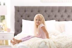 Menina bonito que senta-se na cama com descansos foto de stock royalty free