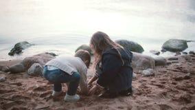 A menina bonito que senta-se na costa e que joga toma a areia à disposição e derrama-a então na terra Irmão que vai à irmã vídeos de arquivo