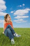 Menina bonito que senta-se na grama verde Foto de Stock