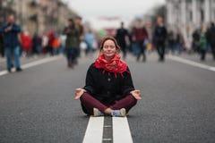 Menina bonito que senta-se na meditação no meio de uma rua movimentada fotos de stock