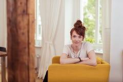 Menina bonito que senta-se na poltrona com os braços cruzados Imagem de Stock Royalty Free