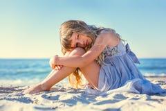 Menina bonito que senta-se na praia do oceano Fotos de Stock Royalty Free