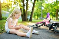 Menina bonito que senta-se na terra após a queda fora sua bicicleta no parque do verão Criança que obtém dano ao montar uma bicic imagem de stock