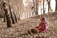 Menina bonito que senta-se nas folhas de outono caídas quando folhas que caem e que jogam com bonecas Imagem de Stock Royalty Free