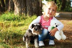 Menina bonito que senta-se no parque com seu cão Fotos de Stock