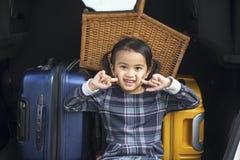 Menina bonito que senta-se no tronco de carro imagem de stock