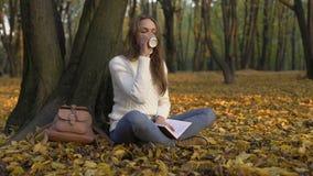 Menina bonito que senta-se sob a árvore no parque, apreciando o café e lendo seu diário filme
