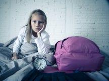 A menina bonito que sente muito cansou-se cedo na manhã que não quer preparar-se para a escola foto de stock royalty free