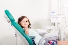 Menina bonito que sorri mostrando o sinal aprovado em dental fotos de stock royalty free
