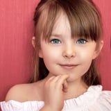 Menina bonito que sorri sobre o fundo cor-de-rosa brilhante imagem de stock royalty free
