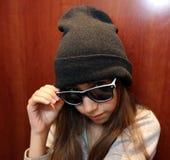 Menina bonito que sorri vestindo os óculos de sol brancos e pretos imagens de stock
