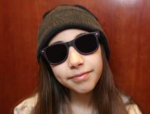 Menina bonito que sorri vestindo os óculos de sol brancos e pretos imagem de stock
