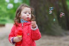 Menina bonito que tem o divertimento com bolhas de sabão imagem de stock royalty free