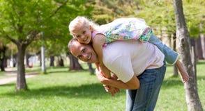 Menina bonito que tem o divertimento com seu pai Fotografia de Stock Royalty Free