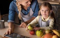 Menina bonito que tem o divertimento com sua mãe na cozinha imagem de stock royalty free