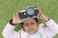 Menina bonito que toma imagens com sua câmera fotografia de stock