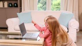 Menina bonito que usa o portátil com mãe filme