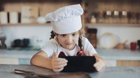 Menina bonito que usa o smartphone durante o café da manhã que senta-se na cozinha É vestida em um avental que olha video estoque
