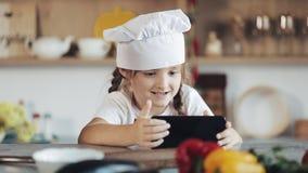 Menina bonito que usa o smartphone durante o café da manhã que senta-se na cozinha É vestida em um avental que olha filme