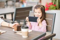 Menina bonito que usa o telefone esperto no café foto de stock