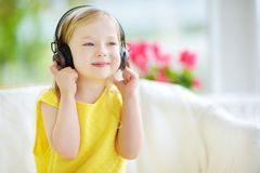Menina bonito que veste fones de ouvido sem fio enormes Criança bonita que escuta a música Estudante que tem o divertimento que e Fotografia de Stock Royalty Free