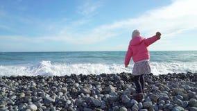 Menina bonito que veste o revestimento cor-de-rosa que joga com as ondas pelo mar no dia de mola frio vídeos de arquivo