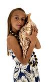 Menina bonito que veste um vestido tropical e que guarda uma grande concha do mar Fotografia de Stock