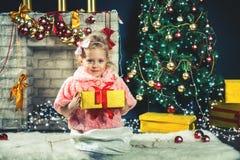 A menina bonito recebe uma árvore de Natal de decoração próxima do presente Imagens de Stock