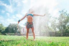 A menina bonito refresca-se da mangueira molhando do jardim fotografia de stock royalty free