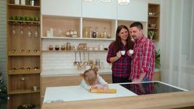 A menina bonito rola a massa quando seus pais felizes beberem o café na cozinha video estoque