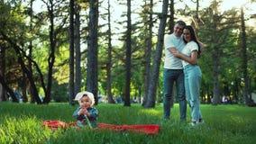 A menina bonito senta-se na grama verde e os pais de amor olham-na de atrás video estoque