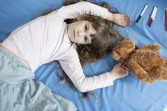 Menina bonito sete anos de encontro velho na cama Fotografia de Stock Royalty Free