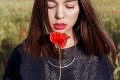 A menina bonito 'sexy' bonita com bordos grandes e o batom vermelho em um revestimento preto com uma papoila da flor que está em  Imagens de Stock Royalty Free