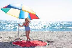 Menina bonito sob um guarda-chuva colorido fotos de stock royalty free