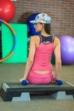 A menina branca bonita nova em um terno cor-de-rosa dos esportes com pesos senta-se em uma etapa antes de treinar em um clube de  imagens de stock