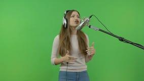 A menina branca canta emocionalmente no microfone do estúdio Grave um grampo da música Em um fundo verde filme