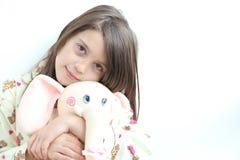 A menina branca loving nos pijamas e o elefante brincam fotografia de stock royalty free