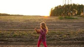 Menina branca nova que aplaude pelas mãos na cena rural do por do sol Dança bonita da menina e vista ao redor video estoque