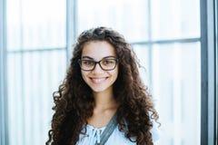 A menina brasileira bonito com cabelo encaracolado e roupa ocasional sorri para a câmera imagem de stock