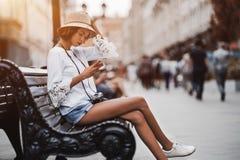 Menina brasileira do toursit no banco com smartphone e câmera foto de stock royalty free